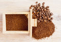 Coffee beans and ground lying side by side on the old board Stock Photo