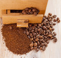 Coffee beans and ground lying side by side on the old board Stock Photos
