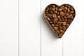 Coffee beans in heart form top view of on white wooden table Royalty Free Stock Photos