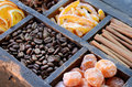 Coffee beans kumquats and spices cinnamon candied peels dried orange slices star anise in rusted wooden crate Stock Photos