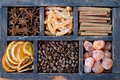 Coffee beans kumquats and spices mix of dried orange slices cinnamon candied peels ans star anise on rusted wooden crate Stock Photos