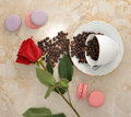 Coffee beans in mug, rose flower cookies and French macarons. to Royalty Free Stock Photo