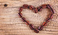 Coffee beans placed in shape of heart on old wooden background Stock Image
