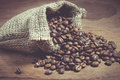 Coffee beans in a sack on wooden background. Royalty Free Stock Photo