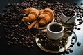 Coffee beans two cups of with croissants and pieces of cinnamon Royalty Free Stock Photography