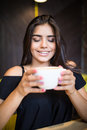Coffee. Beautiful Girl Drinking Tea or Coffee in Cafe. Beauty Model Woman with the Cup of Hot Beverage. Royalty Free Stock Photo