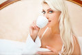 Coffee in bed close up portrait of beautiful blond woman drinking Stock Image