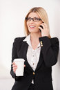 Coffee break confident mature businesswoman talking on the mobile phone and holding a cup Royalty Free Stock Photography