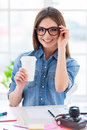 Coffee break confident young business woman sitting at her working place and drinking Stock Photo