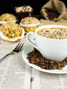 Coffee break cup of roasted beans and a muffin arranged on a newspaper Royalty Free Stock Images