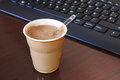 Coffee break in the office a cup of from machine table front of keyboard Royalty Free Stock Photo