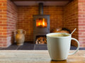 Coffee break by wood burning fire cup on wooden table in front of roaring inside stove in brick fireplace Royalty Free Stock Photo