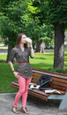 Coffee break young woman standing up near a bench in a park and drinking a hot during a of her work on a laptop Stock Photos