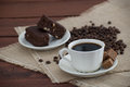 Coffee and brownies dark with brown sugar cubes the bottom plate of chocolate on the wooden table decorated with burlap beans Royalty Free Stock Image