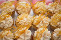 Coffee butterscotch cupcakes with spun sugar decoration rows of brightly colored frosted of toffee flavor a Stock Photo
