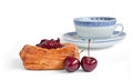 Coffee cake with cherry and a cup two cherries chinese style behind Stock Image