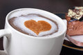 Coffee and cake gourmet fresh brewed mug of cappuccino topped with frothy milk a cinnamon heart with out of focus mocha mousse in Royalty Free Stock Images