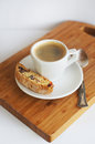 Coffee and cantucci in white cup with one on the wooden board Stock Image