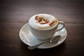 Coffee cappuccino in a white cup on a wooden table Royalty Free Stock Image