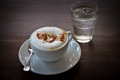 Coffee cappuccino in a white cup on a wooden table Royalty Free Stock Photography