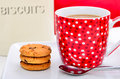 Coffee and chocolate chip cookies in a bright red mug with a biscuit tin in the background Royalty Free Stock Images