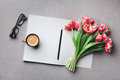 Coffee, clean notebook, eyeglasses and beautiful flower on stone table top view in flat lay style. Woman working desk. Royalty Free Stock Photo