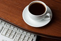 Coffee on computer desk keyboard Royalty Free Stock Photography