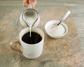 Coffee and cream photo of female hand pouring into a cup of black with stone aged wood underneath Stock Photo