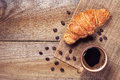 Coffee and croissant for breakfast on a rustic wooden table top view Stock Photos