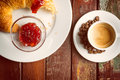 Coffee and croissant on a wooden plate Stock Photos