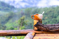 Coffee cup on bamboo coaster and wooden balcony with mountain view Royalty Free Stock Photo