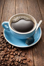 Coffee cup beans a of black with on a rustic wood background Royalty Free Stock Photos