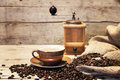 Coffee cup, beans and grinder in front of vintage wooden backgr Royalty Free Stock Photo