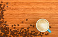 Coffee cup and beans over wood background Royalty Free Stock Photo