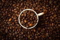 Coffee cup and beans a of surrounded by Royalty Free Stock Images
