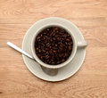 Coffee cup and beans a of with on a wooden background Royalty Free Stock Photography