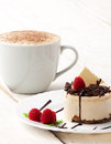 Coffee with cup cake cream and raspberry and chocolate in white plate on wooden white table Royalty Free Stock Images
