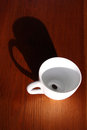 Coffee cup casts shadow Stock Image