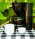 Coffee cup and coffee machine on the garden background Stock Photos