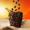 Coffee cup with coffee splash and beans falling on jute bag Stock Photos