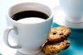 Coffee cup with cookies on blue Royalty Free Stock Images