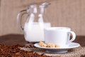 Coffee cup, cream, coffee grains and cane sugar Royalty Free Stock Photo