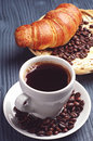 Coffee cup with a croissant on dark wooden table Stock Images