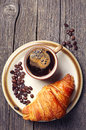 Coffee cup with a croissant on plate on wooden table top view Stock Photography