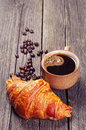 Coffee cup with a croissant on vintage wooden table Stock Photo