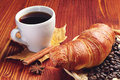 Coffee cup with a croissant on wooden table Royalty Free Stock Images