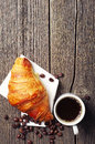 Coffee cup with a croissant on wooden table top view Stock Photography