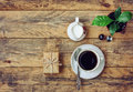Coffee cup, flower pot, milk jug, gift box on wooden table Royalty Free Stock Photo