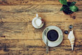 Coffee cup, flower in pot, pitcher of milk on wooden table Royalty Free Stock Photo