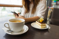 Coffee cup is in front of woman using her smart phone Royalty Free Stock Photo